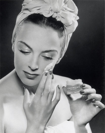 Glamorous woman applying skin cream, 1945-1955.